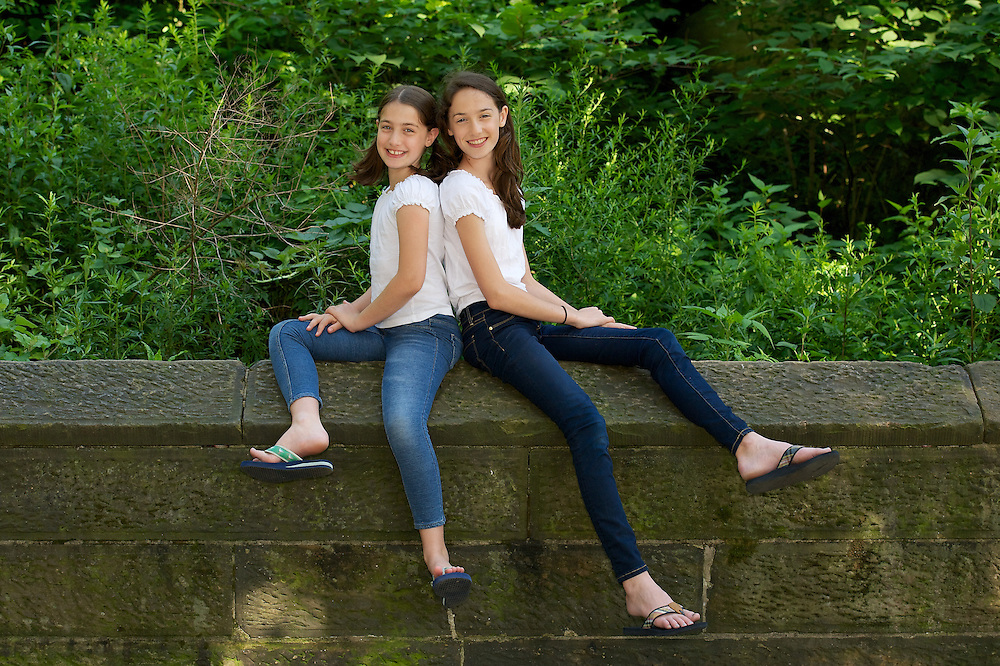 Children's portrait of sisters sitting on stone wall.