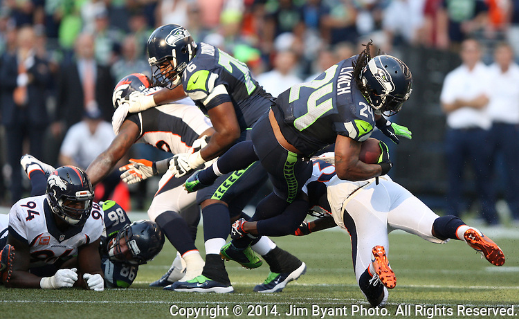 Seattle Seahawks running back Marshawn Lynch (24)is tripped up by   Denver Broncos cornerback Kayvon Webster (36) in overtime at CenturyLink Field in Seattle, Washington on September 21, 2014.   Lynch ran for 88 yards and scored two touchdowns in the Seahawks 26-20 overtime win over the Broncos.  Providing blocking against the Broncos defenders is tackle Russell Okung (76)  and tight end Zach Miller (86)  ©2014. Jim Bryant Photo. All rights Reserved.