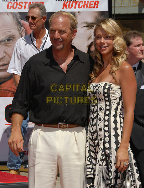 KEVIN COSTNER & CHRISTINE BAUMGARTNER.At The Kevin Costner Hand & Footprint Ceremony held at The Grauman's Chinese Theatre in Hollywood, California, USA..September 6th,2006 .Ref: DVS.half length black shirt white trousers strapless pattern dress .www.capitalpictures.com.sales@capitalpictures.com.©Debbie VanStory/Capital Pictures