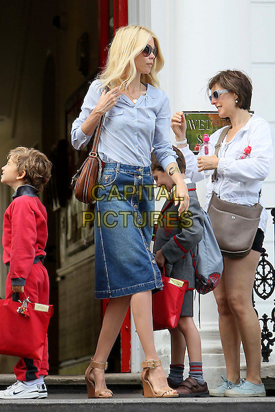 Claudia Schiffer on the school run.London, England..June 28th, 2011.full length blue shirt jean denim skirt buttons brown leather bag satchel wedges shoes sandals sunglasses shades profile.CAP/HIL.©John Hillcoat/Capital Pictures .
