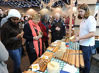 NWA Media/ANDY SHUPE - Kent Walker of Walker Artisan Cheese in Little Rock slices cheese Saturday, Dec. 6, 2014, during The Little Craft Show in the Fayetteville Town Center. The show featured works from local and area vendors.
