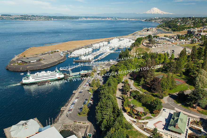 With Mt. Rainier and the Point Defiance Park and Marina in the background, the Point Defiance-Tahlequah ferry boat loads cars at the ferry terminal.