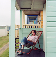 Amanda Lambert sitting in a deck chair outside her beach hut