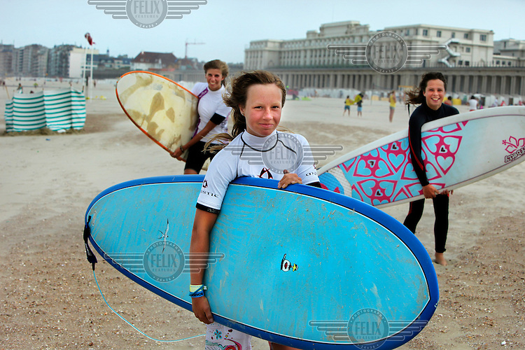 Three girls carry surfboards on the beach at Ostend. .