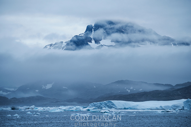 Mountain emerges from misty sea near Tasiilaq, east coast of Greenland