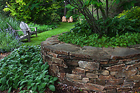 Dry stack stone retaining wall by lawn path with adirondack chairs; Taylor garden