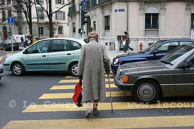 Genève, le 20.02.2008.Pesrsonne agée, traversant un passage piéton entre deux véhicules..© Le Courrier / J.-P. Di Silvestro