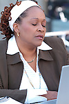 African American woman working on laptop, looking exhausted