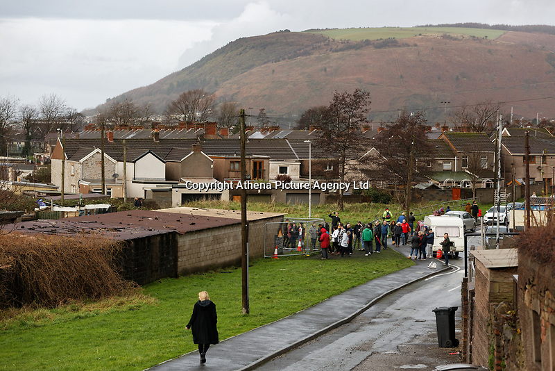"""Pictured: Crowds arrive to see and take pictures of the Banksy graffiti on a garage in Port Talbot, Wales, UK. Thursday 20 December 2018<br /> Re: The artist Banksy has confirmed that a new graffiti piece that has appeared in Port Talbot, south Wales is his.<br /> He announced on Instagram: """"Season's greetings"""" - with a video of the artwork in the Taibach area of Port Talbot.<br /> The image appears on two sides of a garage in a lane near Caradog Street, depicting a child enjoying snow falling - the other side reveals it is a fire emitting ash.<br /> The owner of the garage said he had not slept over fears it might be vandalised."""