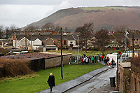 Pictured: Crowds arrive to see and take pictures of the Banksy graffiti on a garage in Port Talbot, Wales, UK. Thursday 20 December 2018<br /> Re: The artist Banksy has confirmed that a new graffiti piece that has appeared in Port Talbot, south Wales is his.<br /> He announced on Instagram: &quot;Season's greetings&quot; - with a video of the artwork in the Taibach area of Port Talbot.<br /> The image appears on two sides of a garage in a lane near Caradog Street, depicting a child enjoying snow falling - the other side reveals it is a fire emitting ash.<br /> The owner of the garage said he had not slept over fears it might be vandalised.