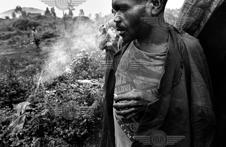 ©Chris Keulen/Panos Pictures..Pygmys smoking marihuana at 6 a.m. in outskirts of Kitshanga-village. About 300 pygmys live together in the periphery of town, unable to live in the woods, marginalised as ever, but because of war even worse. To forget their situation they smoke a lot of marihuana...Democratic Republic Congo (formerly Zaire),  Kitshanga (North-Kivu), 26/10/2001