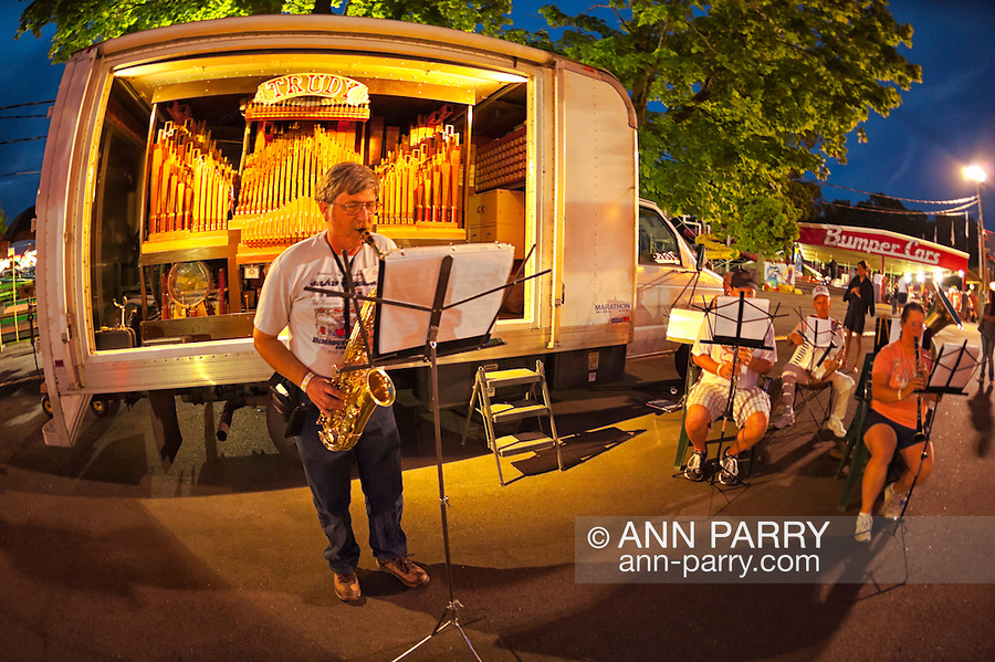 "August 25. 2012 - Middlebury, Connectiicut, U.S. - DAVID WASSON plays saxophone as he stands in front of his home made 98 keyless concert band organ ""Trudy"", along with other musicians, at night concert at Band Organ Rally that Quassy Amusement Park hosts for COAA Carousel Organ of America Association. View taken with 180 degree fisheye lens."