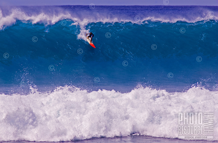 A surfer drops into a large, powerful wave at La Perouse, Maui.