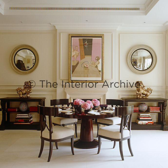 A Francis Bacon print hangs above the dining room fireplace between a pair of symmetrical round mirrors and 19th century matching console tables by Paolo Moschino for Nicholas Haslam