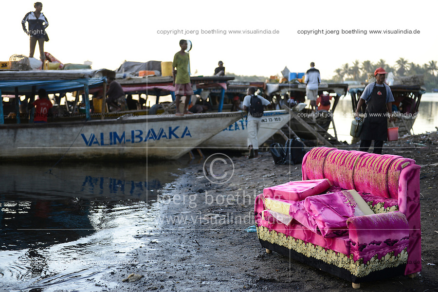 MADAGASCAR, Mananjary, canal des Pangalanes, evening at boat jetty, pink sofa for shipment by boat / MADAGASKAR Mananjary, abends am Bootsableger, von hier werden Waren in die Doerfer am canal des Pangalanes verschifft, Sofa steht fuer Verschiffung bereit