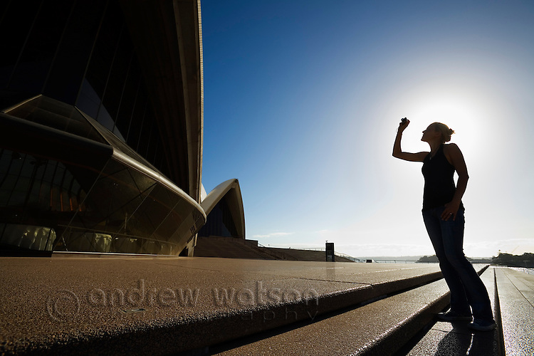 A woman photographs the Sydney Opera House from its steps.  Sydney, New South Wales, AUSTRALIA.