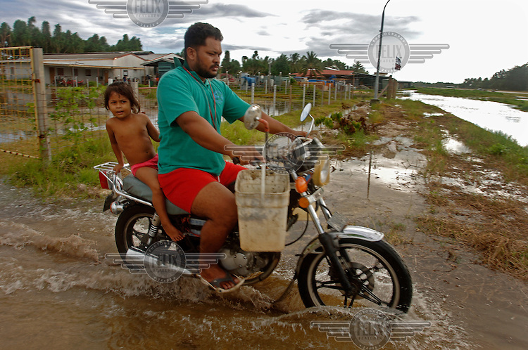 A man with a child on a motorbike negotiates floodwaters on his return from feeding his animals.  The coral atoll is to vulnerable to sea level rise, particularly at high spring tides, when salty water seeps up through the ground and causes flooding....