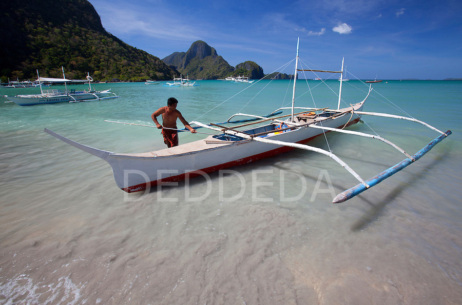 A man secures his wooden bangka boat in the bay at El Nido, Palawan, Philippines, the gateway to the Bacuit Archipelago.