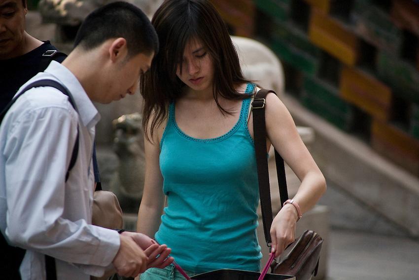 Deux jeunes chinois allument des bâtonnets d'encens avant d'effectuer leur supplique.