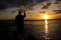 "Man in silhouette against sunset, holidng hand up in ""Shaka"" (""hang loose"") sign. Waikiki, Honolulu, Hawaii"