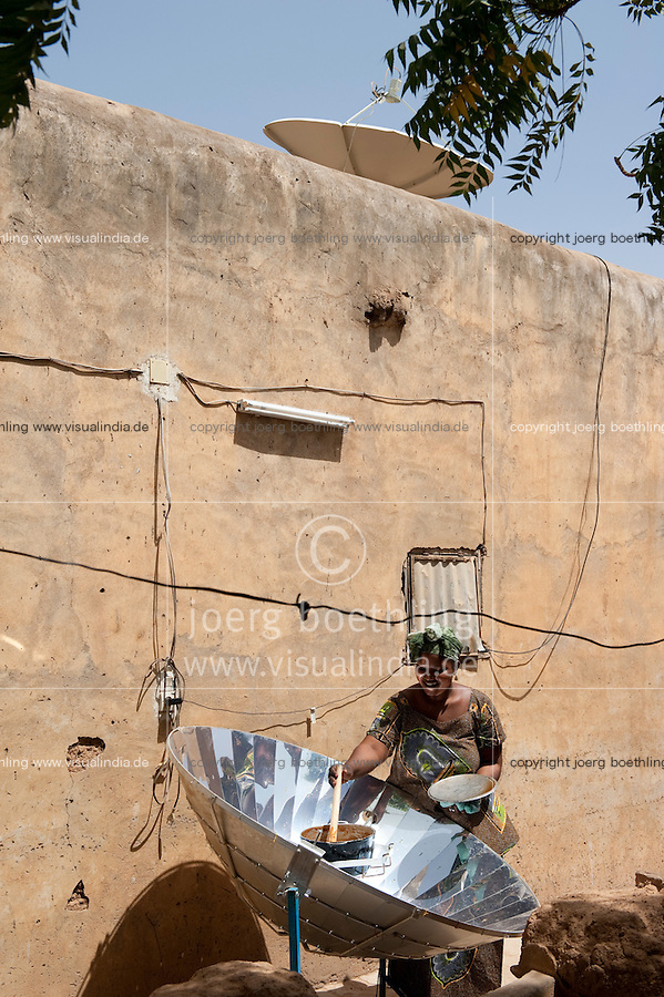 Africa MALI Bandiagara, woman with solar cooker preparing food
