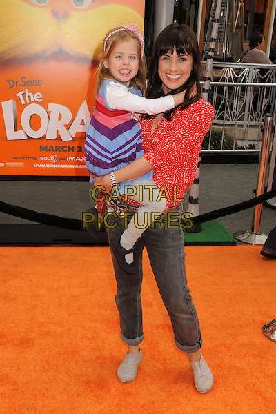 "guest & Constance Zimmer.'Dr. Suess' ""The Lorax"" L.A. Premiere held at The Universal City Walk Theatre in Universal, Los Angeles, California, USA..February 19th, 2012.full length blue purple red top carrying holding kid child jeans denim.CAP/ADM/BP.©Byron Purvis/AdMedia/Capital Pictures."