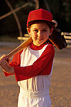 Young girl (7 years old), Little League Baseball player with bat and glove on shoulder, sunset light, portrait, Woodinville, Washington USA  MR