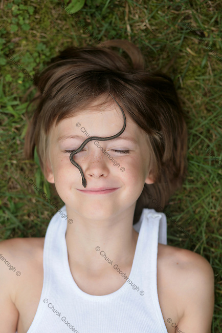 Stock Photo Image of Young Boy lying in the grass with a baby snake crawling across his face