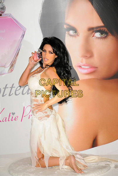 "KATIE PRICE aka JORDAN.photocall to launch her new perfume ""Besotted"" at The Paper Club, Cafe Royal, Regent Street London, England 24th September 2008 .fragrance  full length white lace lingerie sheer kneeling bra  black hair extensions hand on hip.CAP/CAN.©Can Nguyen/Capital Pictures"
