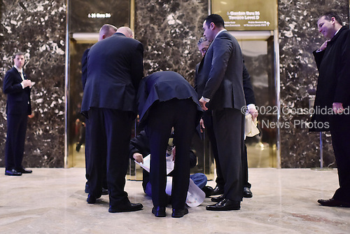 Security team members surround a man sitting in front of the elevator bank in the Trump Tower lobby as he speaks in Spanish and tries to hold up a picture in New York, NY, on January 4, 2017. <br /> Credit: Anthony Behar / Pool via CNP