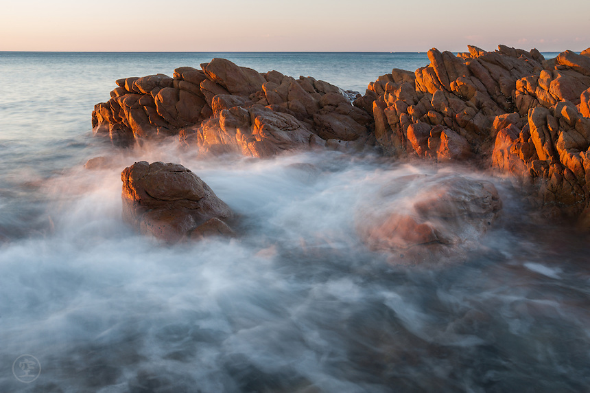 Rocks, where I played as a child, catch the red light of the setting sun... and a sea-mist of breaking waves at evening.