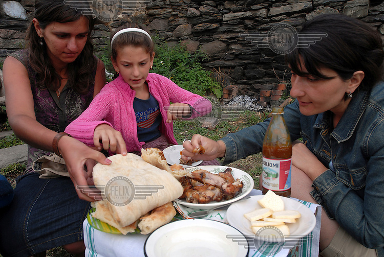 Family enjoy a barbeque at their rented farmhouse - a popular weekend activity for city dwellers escaping from the capital - high up in the mountains of the Kazbegi Valley.