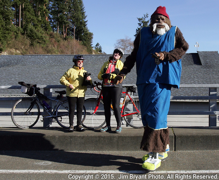 A man dressed in a Bigfoot costume walks on stilts past two bicyclists during the 31st annual Polar Bear into the Burley lagoon on January 1, 2015 in Olalla, Washington. Over 500 hardy participants joined in on the annual New Year's Day Tradition by jumping into the chilly lagoon waters during the Polar Bear Plunge.  ©2015.  Jim Bryant Photo. All Rights Reserved.