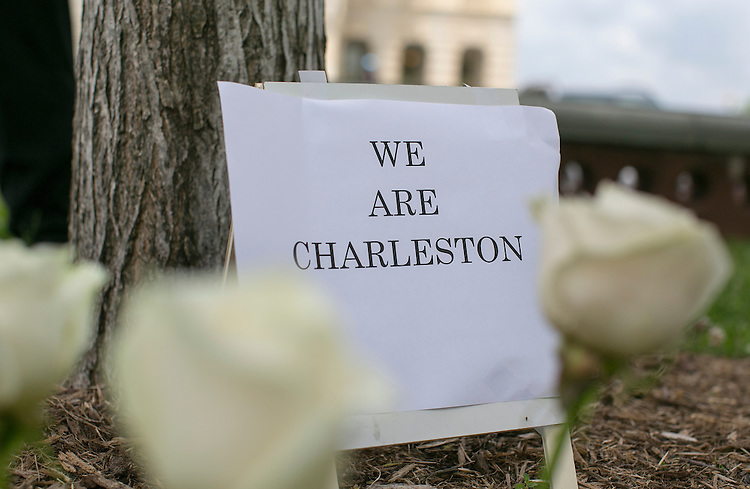 "UNITED STATES - JUNE 18 - White roses are placed beside a sign that reads ""We are Charleston"" underneath a tree during a prayer vigil for victims of the Charleston shooting, outside of the U.S. Capitol on Thursday, June 18, 2015. (Photo By Al Drago/CQ Roll Call)"