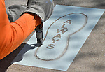 "Pete Milton, a foreman from the Bazan Painting Company in Olivette, uses sandblasting equipment to etch the word ""always"" into one of 20 concrete sidewalk slabs leading to the area where the statue of Robert Wadlow - the ""Alton Giant"" - is displayed in Alton, Illinois. Small pieces of sand are shot at about 50 psi (pounds per square inch) onto the concrete. The rectangular rubberized template outlines the area that will be sandblasted.  The footsteps are a size 37, which was Wadlow's shoe size and are spaced to approximate the gait of Wadlow walking. The visual literary art piece, in the 2800 block of College Avenue, is the brainchild of Aaron Williams, founder and champion of the 7th Grade Poetry Foundation based in St. Louis. Work was being done on Thursday April 26, 2018."