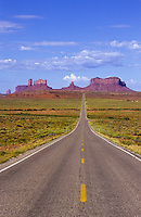 The road with yellow stripes leading to Monument Valley National Park and navaho Indian reservation,  Utah, USA
