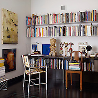 Metal bookshelves line the wall of the office with an aluminium and nylon chair designed by de Vera and artworks by Darren Waterston, David LaChapelle and Cindy Sherman