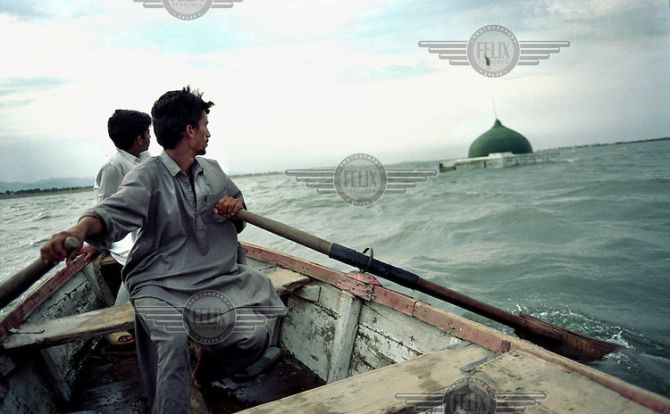 Two men in a fishing boat row towards the muslim shrine which remains submerged in the reservoir created by the Mangla Dam.  The Mangla dam project in the 1960s displaced over 100,000 people when water innundated surrounding settlements.  .