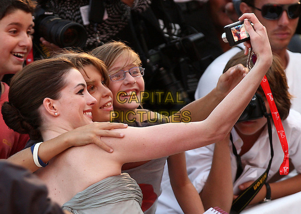 "ANNE HATHAWAY & FANS.""Rachel Getting Married' premiere during the 65th Venice Film Festival, Venice, Italy..September 3rd, 2008.half length grey gray strapless dress profile arm taking picture photograph .CAP/ADM/Liverani.©Liverani/AdMedia/Capital Pictures"