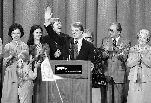 """United States President-elect Jimmy Carter, surrounded by family, acknowledges the cheers of the crowd at an election night rally as he claims victory over US President Gerald R. Ford in Atlanta, Georgia on November 3, 1976.  <br /> Credit: Benjamin E. """"Gene"""" Forte / CNP"""