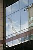 Construction crane reflected in office block window UK