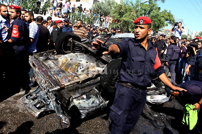 Palestinian security men disperse people as they gather to inspect the wreckage of a car following a blast in Gaza City November 3, 2010. The car exploded outside a police headquarters in the city of Gaza on Wednesday, killing one Palestinian, Hamas officials and witnesses said. The Hamas Interior Ministry said the explosion was caused by an Israeli air strike . Photo by Ashraf Amra