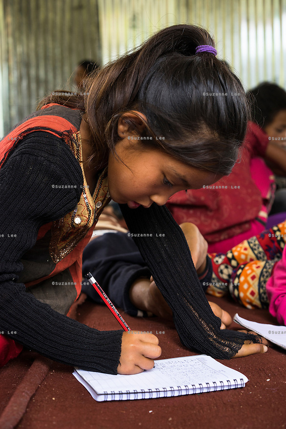 Children write lines in their notebooks as a teacher helps them learn basic english in the SOS Children's Villages Child Care Space in Rayale, Nepal on 1 July 2015. The Child Care Space was set up by SOS Children's Villages soon after the earthquake so that they children of the village can come together to play, learn, and get over the trauma of the disaster, while their parents can be free to reconstruct their homes and go off to get rations and relief kits. Photo by Suzanne Lee for SOS Children's Villages