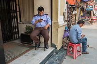 Nepal, Kathmandu. Men checking their phones.
