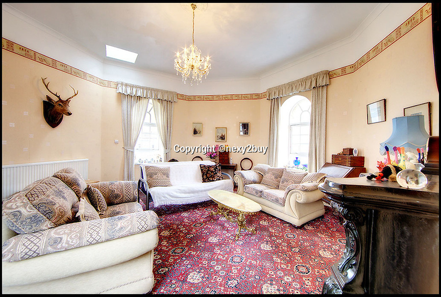 BNPS.co.uk (01202 558833)<br /> Pic: next2buy/BNPS<br /> <br /> ***Please use full byline*** <br /> <br /> The living room.<br /> <br /> An Englishman's home is his castle...<br /> <br /> An incredible property that looks like a miniature castle has come on the market for the bargain price of &pound;250,000.<br /> <br /> The Grade II listed building was erected in 1720 and features an amazing turret that boasts countryside and harbour views.<br /> <br /> It was originally used as a watch tower and the rest of the building was used as an office by the harbour master.<br /> <br /> The building, which is in Whitley Bay, Tyne and Wear, boasts four bedrooms, an open plan kitchen and dining room, and a spacious living room.<br /> <br /> It also has a yard at the back and is just a stone's throw away from the stunning coastal walk surrounding Colywell Bay.<br /> <br /> The property is being sold through Next2Buy estate agents who are based in Tyneside.