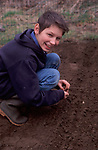 AE2BX1 Young boy planting vegetable seeds in the garden