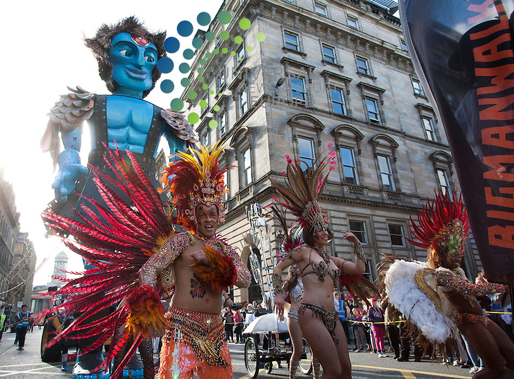 Big Man Walking, a 26ft high puppet moving at 1mph, will travel through to the Merchant City Area leaving from George Square during the festival performances. Pictured: Performers dance in the parade. 27th July 2012. Picture: Jonathan Faulds / Universal News And Sport (Europe)