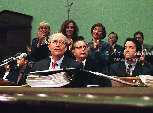 Special Prosecutor Kenneth Starr enjoys applause after completing his testimony at a United States House Judiciary Committee hearing on pending Articles of Impeachment against U.S. President Bill Clinton on Capitol Hill in Washington, D.C. on November 19, 1998. Spokesman Charles Bakaly, seated directly right of Starr, appears shocked by the spontaneous demonstration..Credit: Ron Sachs / CNP