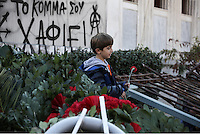 Pictured: A boy leaves a red carnation at the monument for the uprising at the Athens Polytechinc in Athens Greece. Thursday 17 November 2016<br /> Re: 43rd anniversary of the Athens Polytechnic uprising of 1973 which was a massive demonstration of popular rejection of the Greek military junta of 1967–1974. The uprising began on November 14, 1973, escalated to an open anti-junta revolt and ended in bloodshed in the early morning of November 17 after a series of events starting with a tank crashing through the gates of the Polytechnic.