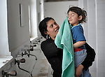 Gabriela Iseni, 4, a Roma girl whose family was displaced by a severe cold spell, gets her face cleaned by her mother, Juntena Iseni, in a temporary shelter established by the Red Cross in Smederevo, Serbia. Church World Service has provided this family and others with food and other emergency supplies.